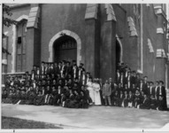 Class of 1907 in graduation gowns outside the...