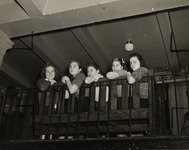 Five women students seated on a bench. Photograph...