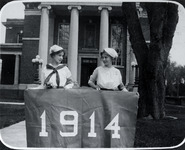 Two women students holding the class of 1914...
